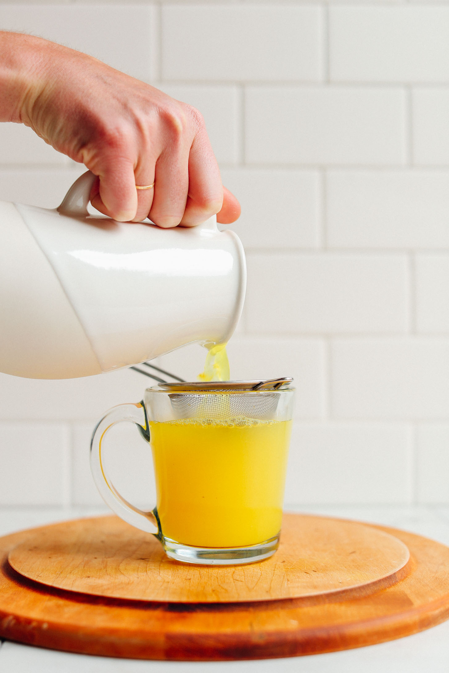 Pouring Turmeric Ginger TONIC through a strainer into a glass mug