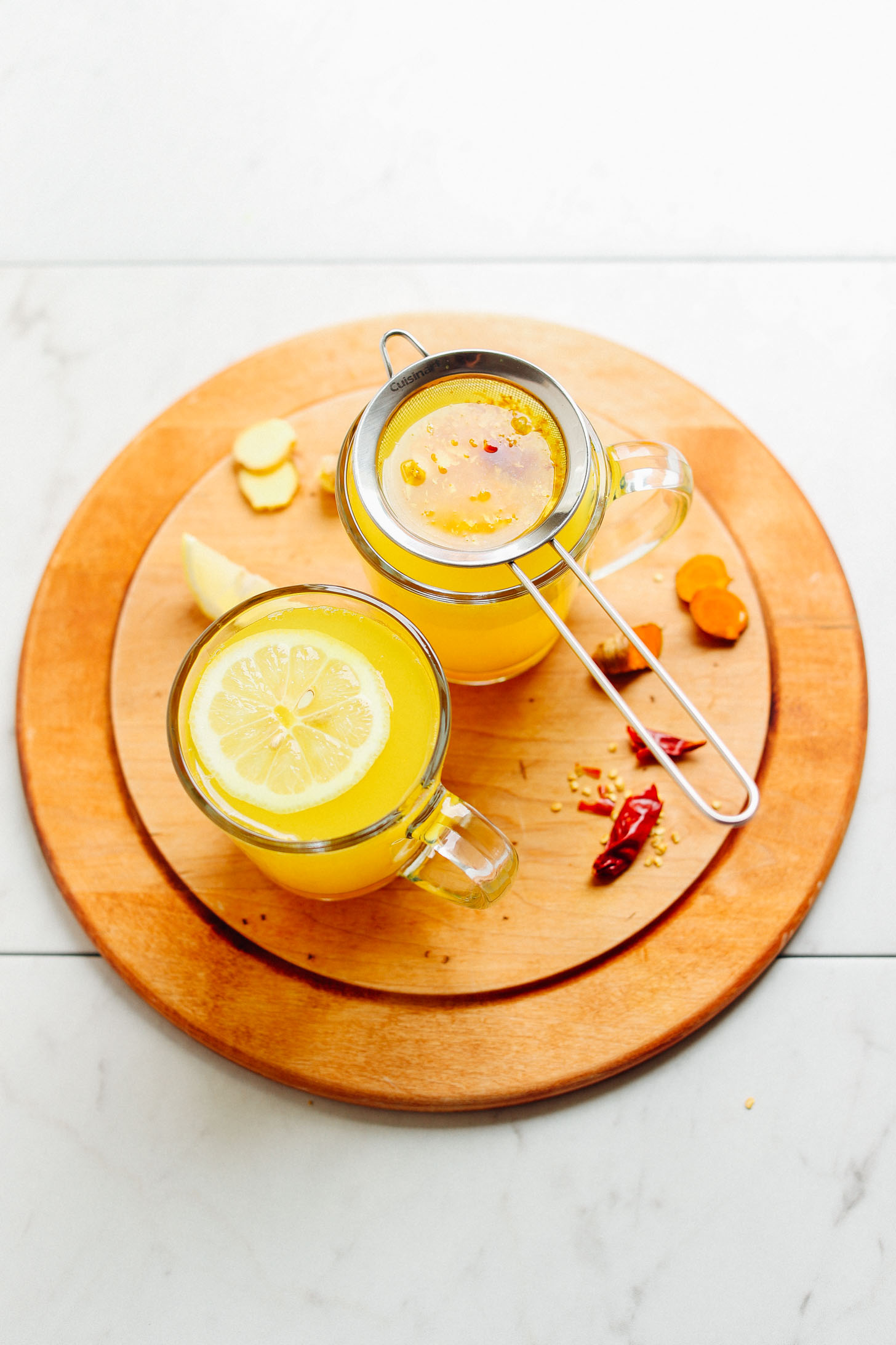 Mugs of healing Turmeric Ginger TONIC displayed on a cutting board with ingredients