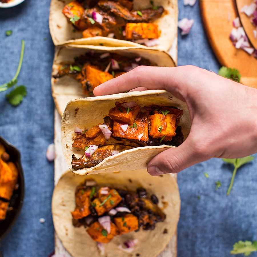 Holding a butternut squash taco for our roundup of 16 Vegan Entrees for Stress-Free Cooking