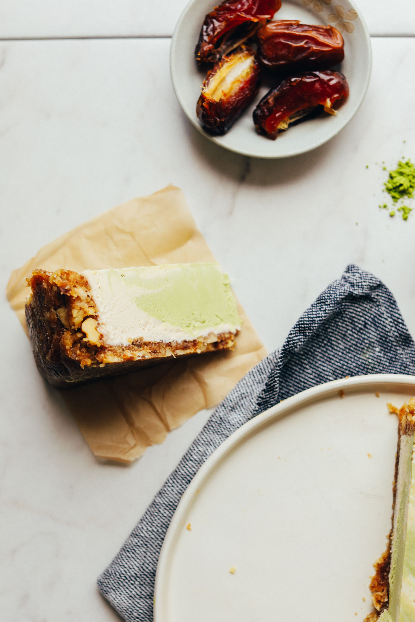 Slice of Matcha Swirl Cheesecake on a parchment paper square ready to be devoured for a delicious plant-based dessert
