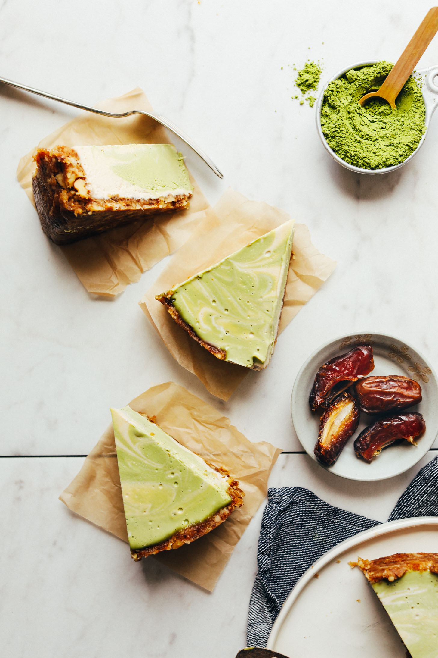 Slices of gluten-free vegan Matcha Swirl Cheesecake on squares of parchment paper