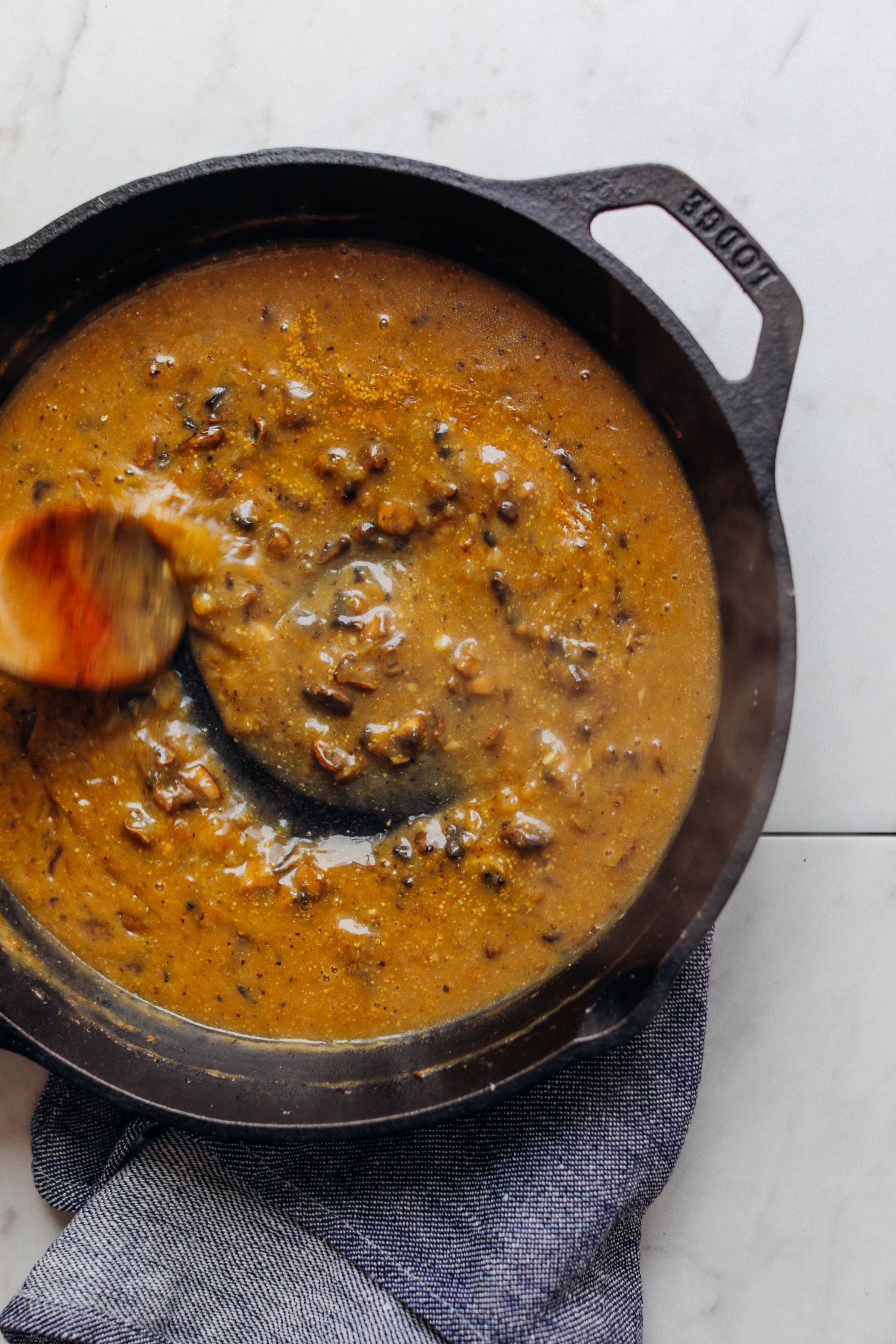 Using a wooden spoon to stir mushroom gravy in a cast iron skillet