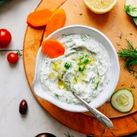 Bowl of flavorful Vegan Tzatziki on a wood cutting board