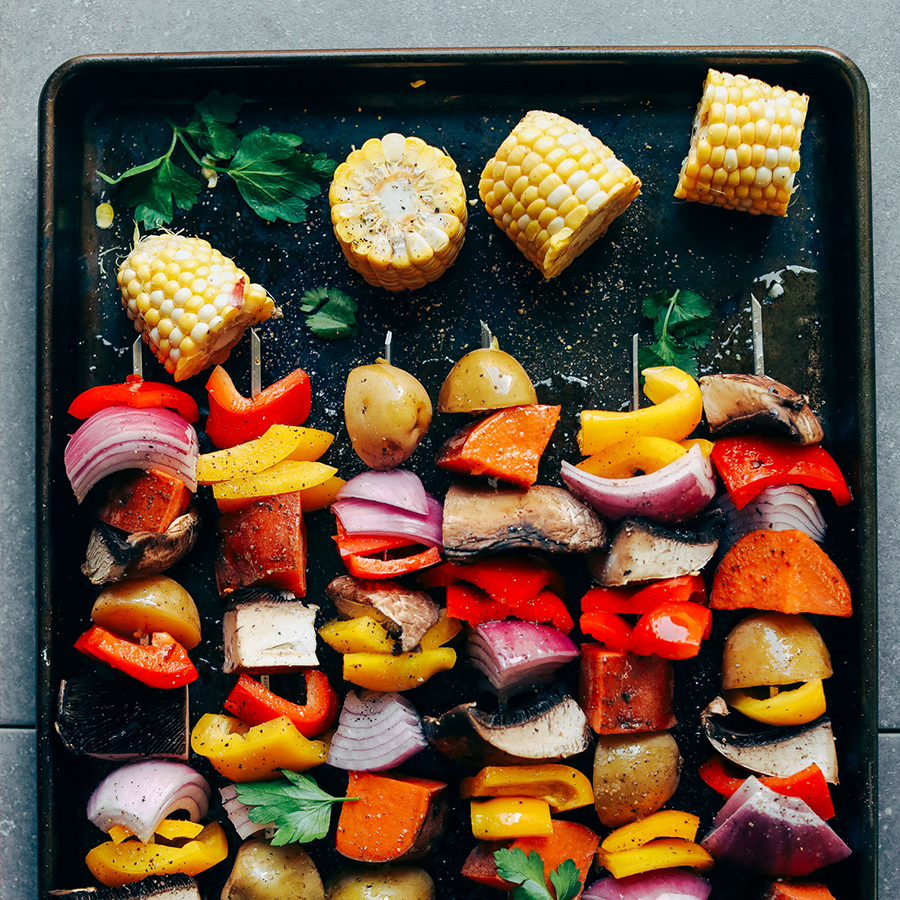 Veggie skewers and corn on the cob on a baking sheet for our 16 Plant-Based Recipes for Labor Day Weekend recipe roundup