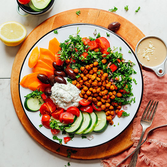 Plate filled with our Easy Greek Bowl recipe surrounded by tahini sauce, lemon, and sliced vegetables