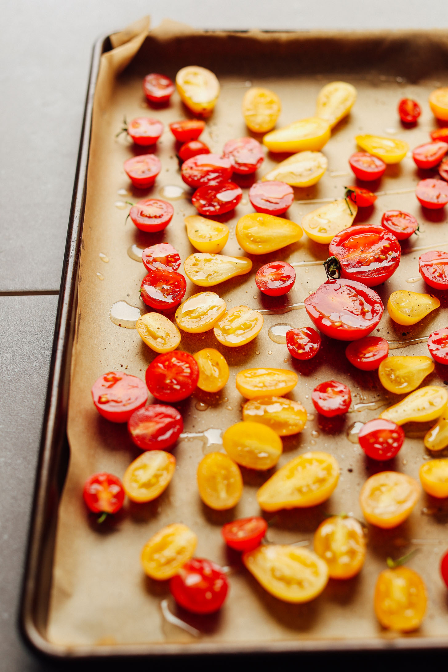 Baking sheet filled with red and yellow Slow Roasted Cherry Tomatoes for adding to salads and more