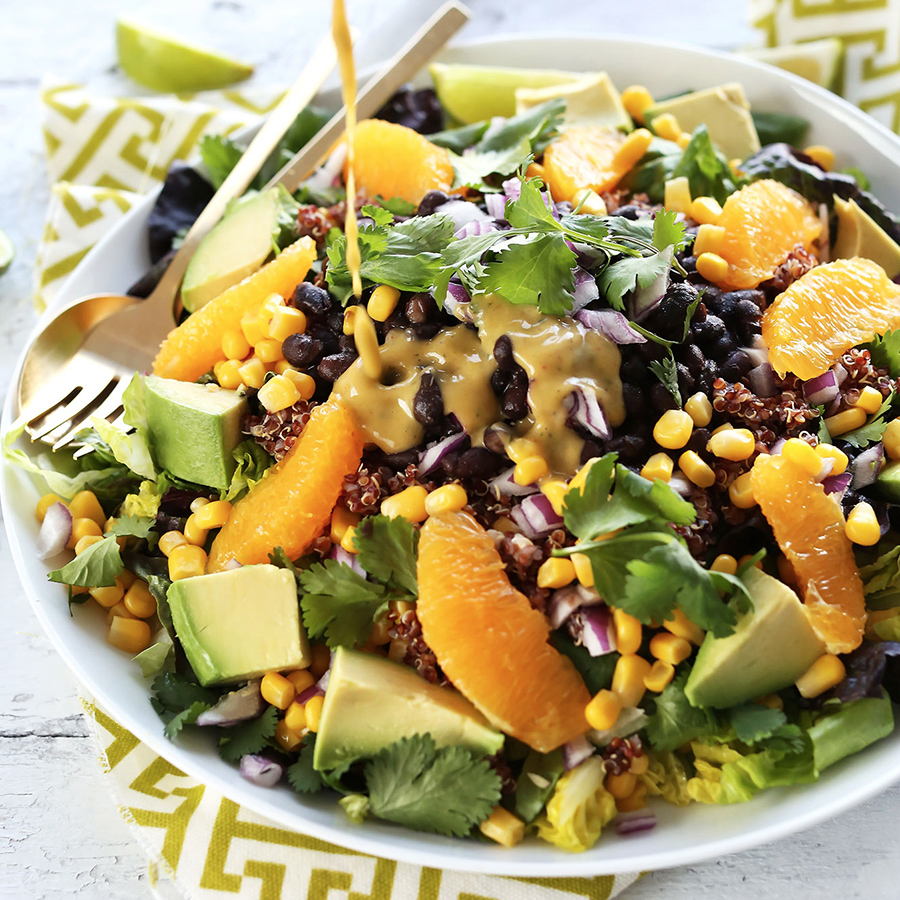 Drizzling Creamy Orange Chili Dressing onto a big bowl of Vegan Mexican Quinoa Salad