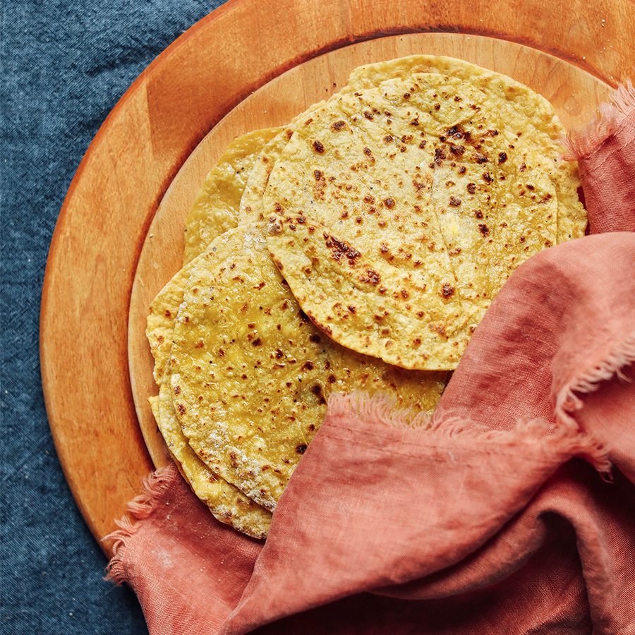 Freshly made Plantain Tortillas and a pink linen on a cutting board