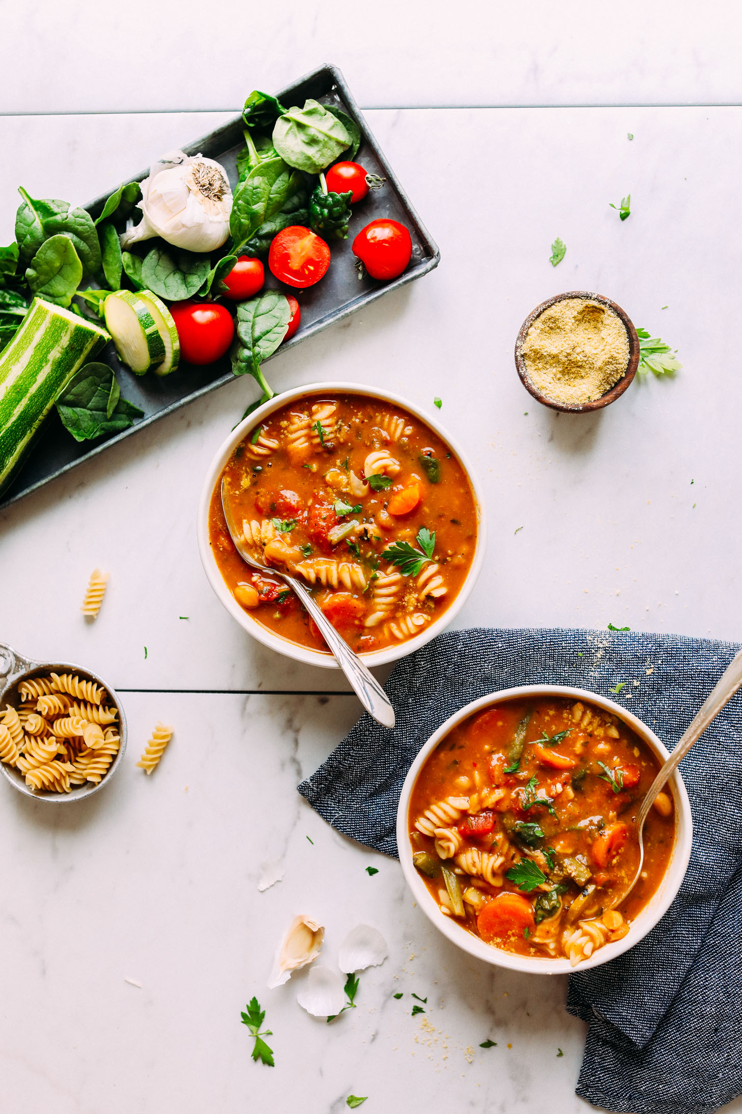 Two bowls of 1-Pot Vegan Minestrone alongside fresh vegetables used to create it
