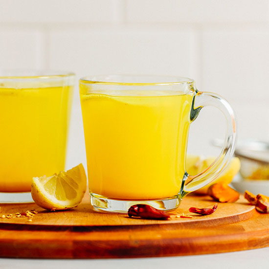 Two glass mugs of our Turmeric Tonic drink on a wood cutting board