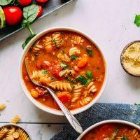 Bowl of Vegan Minestrone beside vegetables, vegan parmesan, and gluten-free noodles