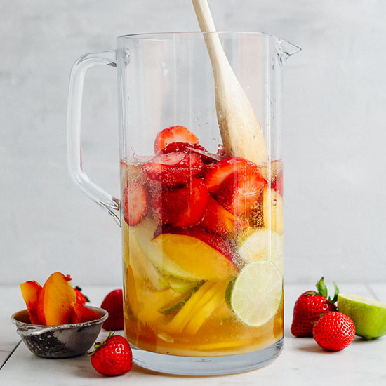 Using a wooden spoon to stir fresh fruit for making White Sangria