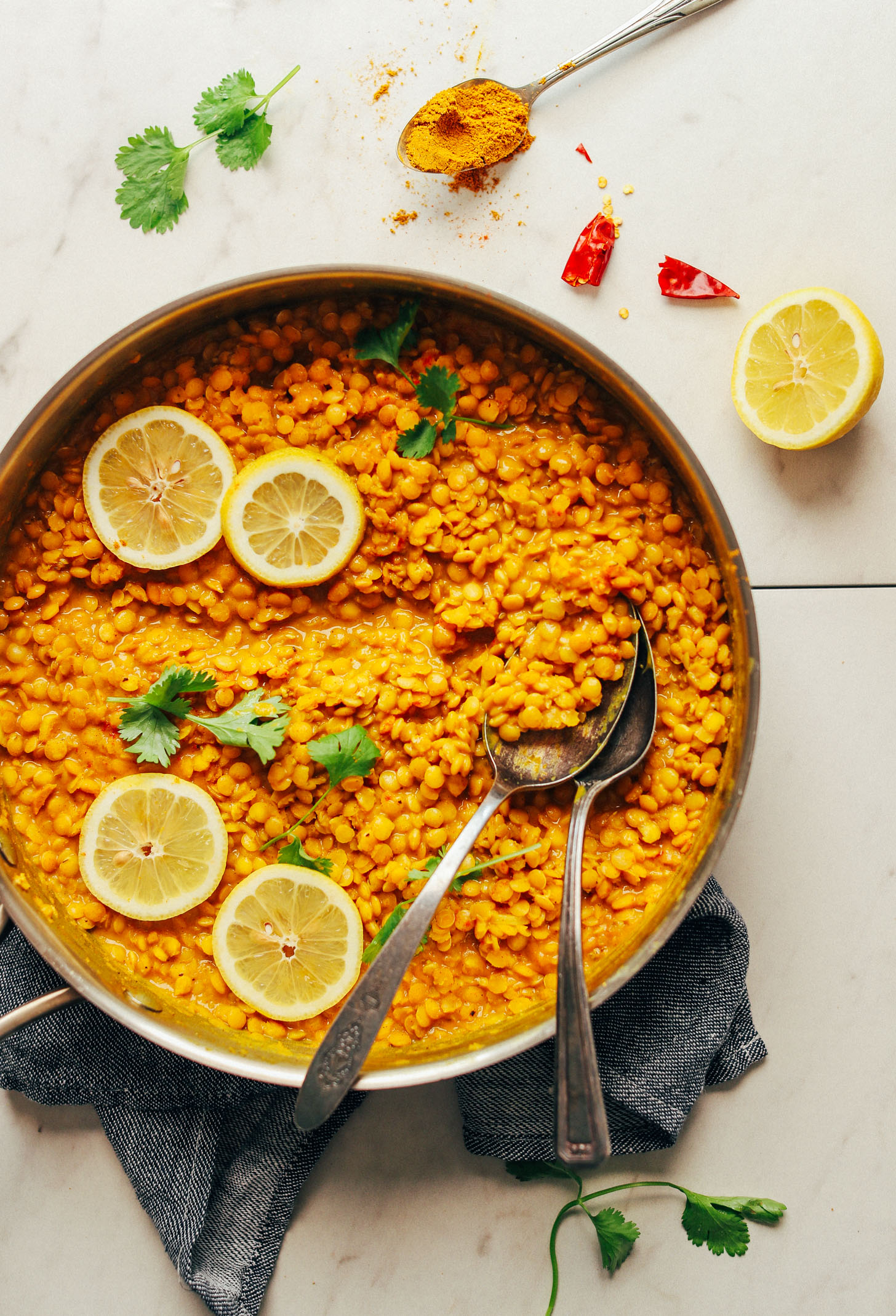 Large pan of vegan gluten-free Coconut Curried Golden Lentils with fresh lemon slices