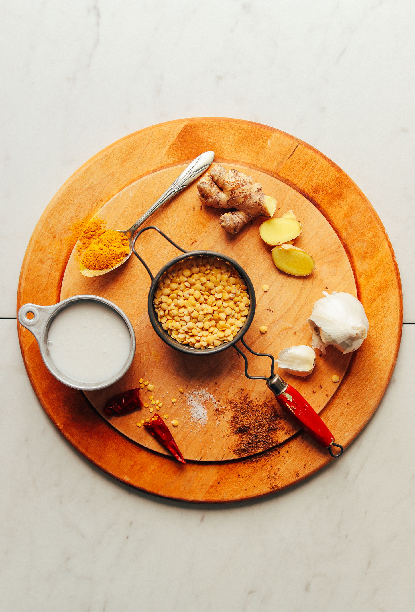 Wood serving platter with ingredients for making vegan Coconut Curried Golden Lentils