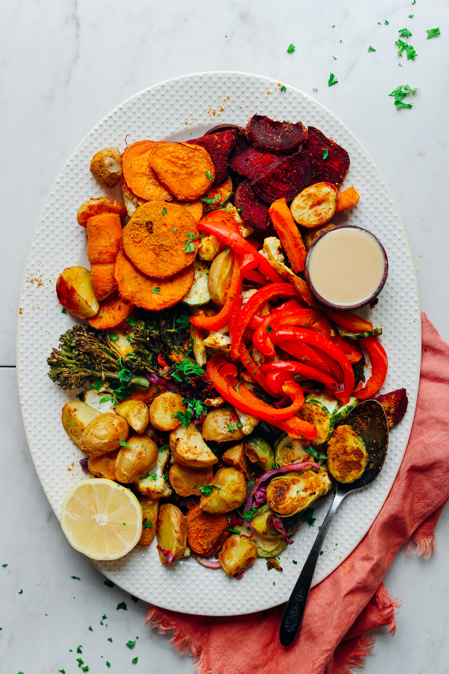 Serving platter filled with colorful Oil-Free Roasted Vegetables with lemon and tahini for serving