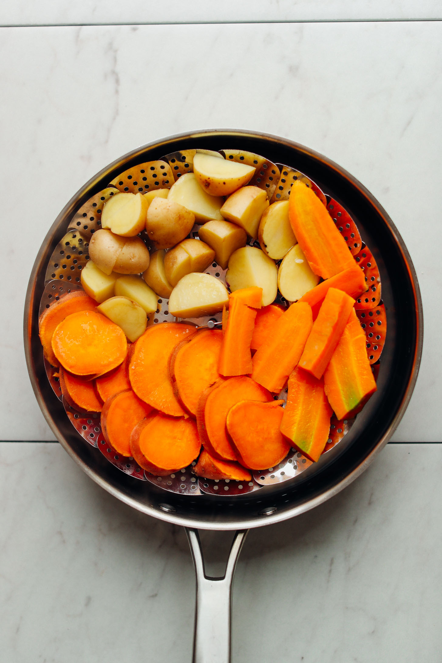 Steam basket filled with chopped potatoes, sweet potatoes, and carrots ready to be softened before roasting