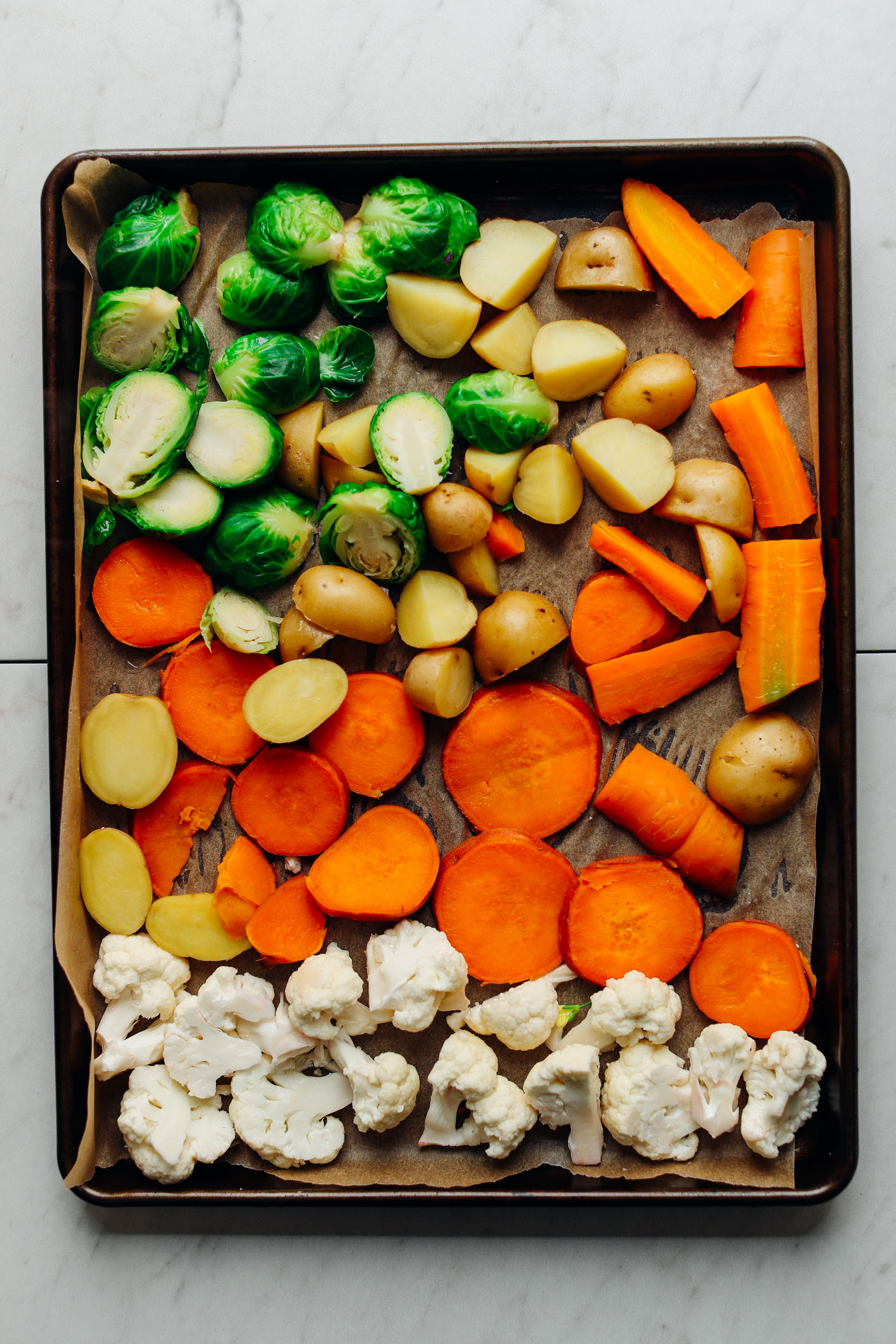 Baking sheet of chopped cauliflower, sweet potatoes, carrots, potatoes, and Brussels Sprouts ready for roasting