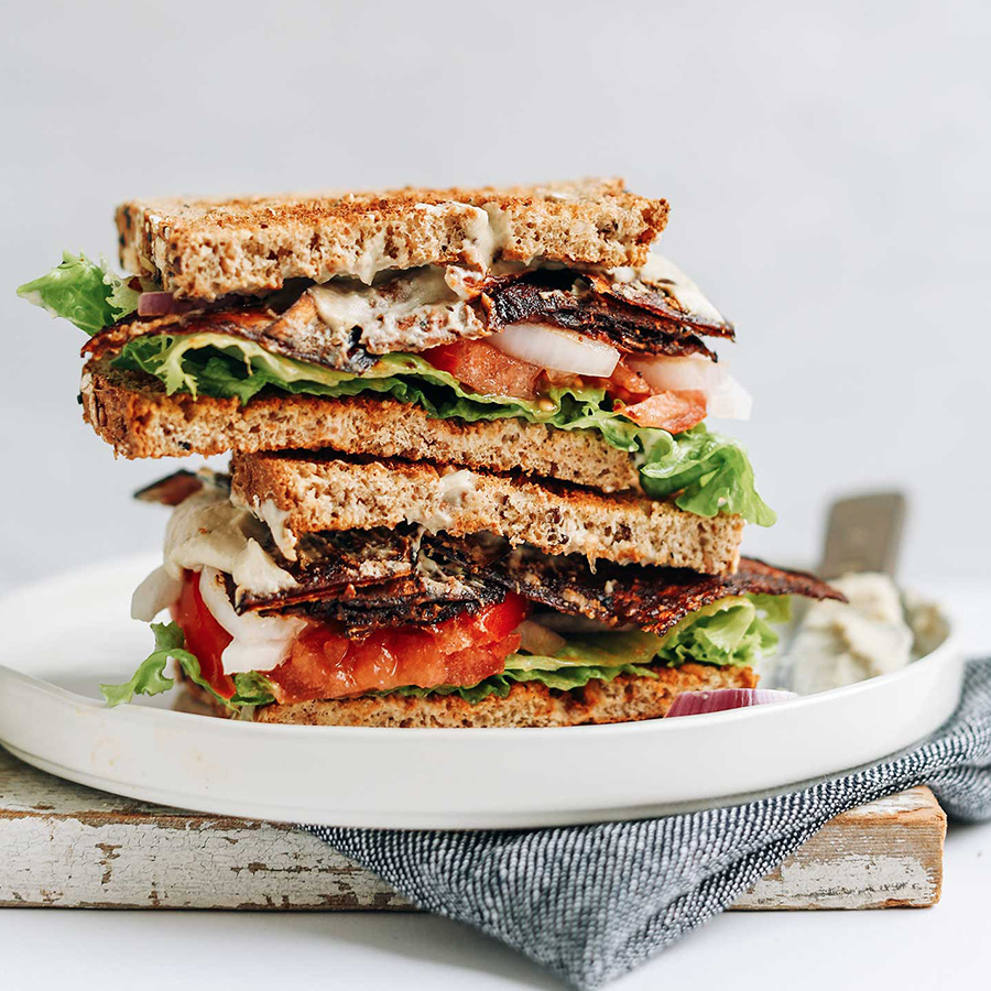 Vegan BLT halves stacked on a plate for our roundup of Lunchbox Recipes