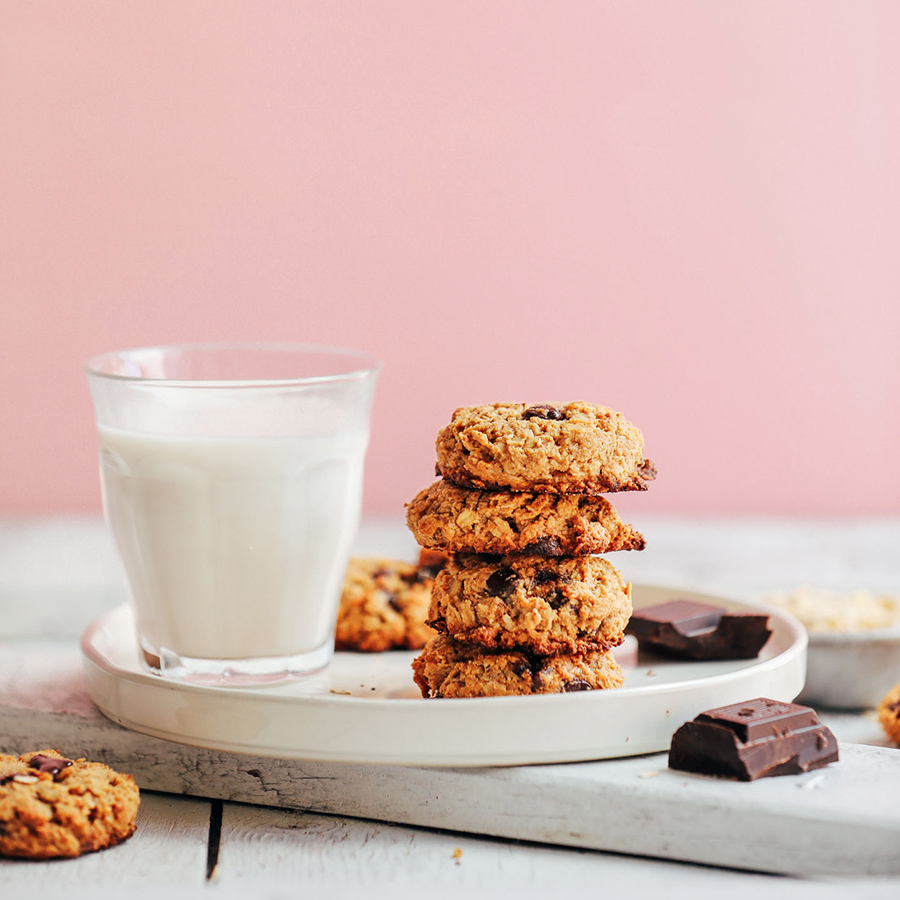 Stack of Oatmeal Chocolate Chip Cookies and almond milk for one of our 10 Vegan Lunchbox Ideas
