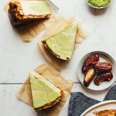 Slices of Vegan Matcha Cheesecake beside dates and matcha powder
