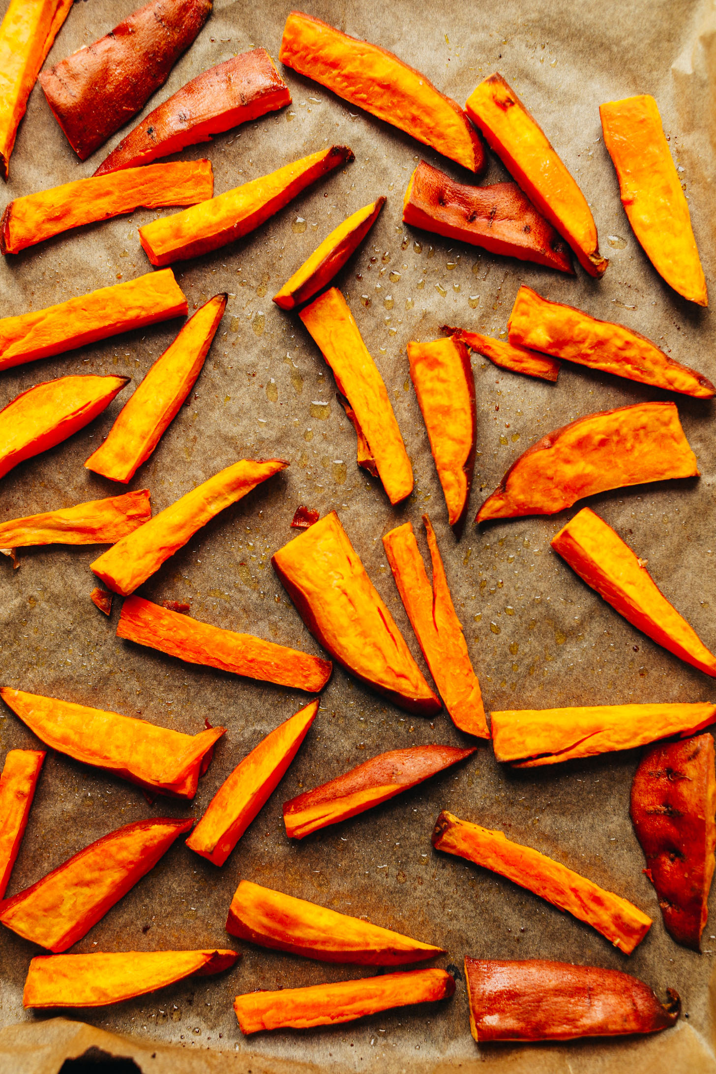 Freshly roasted sliced sweet potatoes on a parchment-lined baking sheet