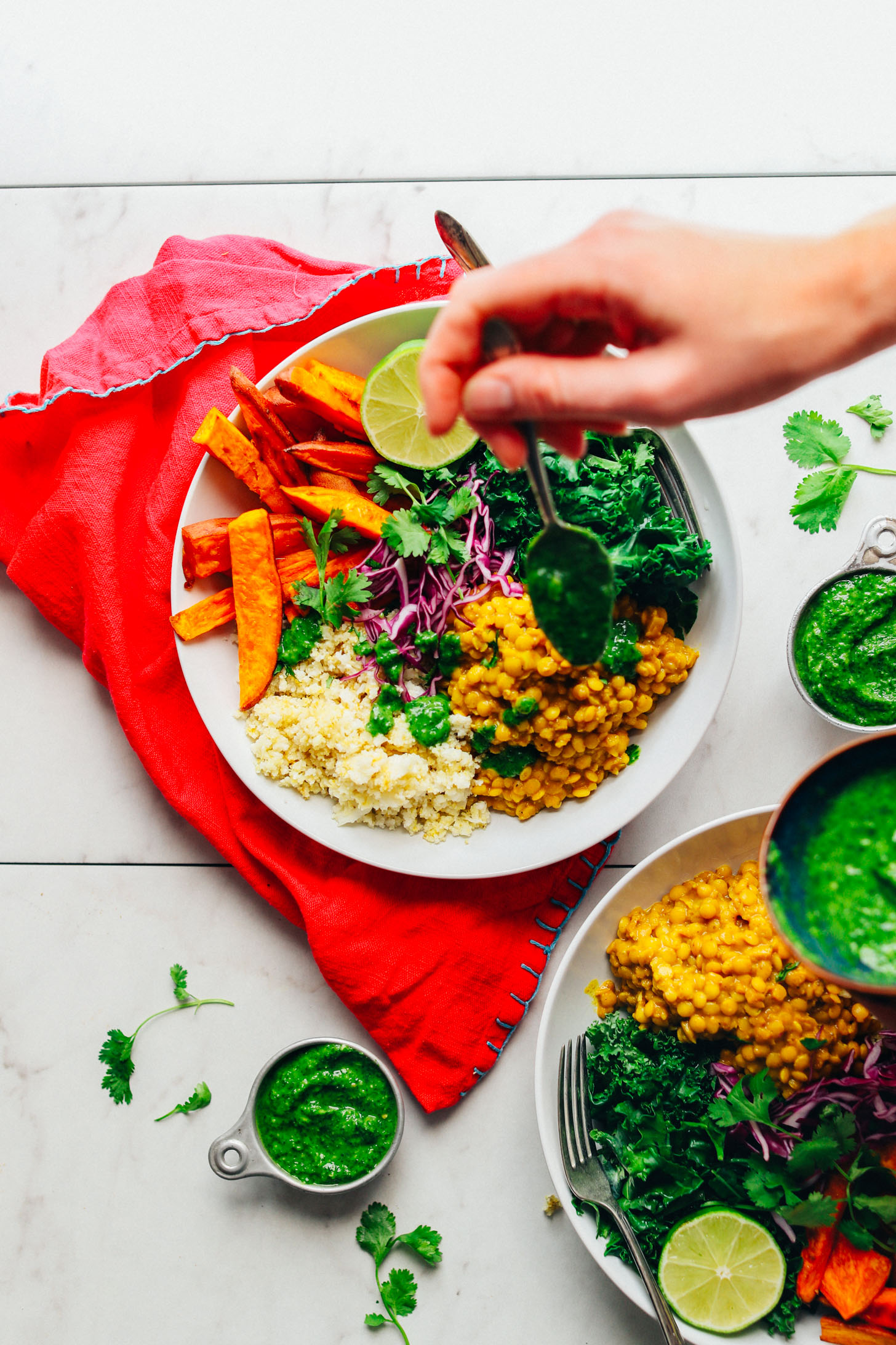 Drizzling cilantro chutney over a Curried Lentil Sweet Potato Bowl for a nourishing plant-based meal