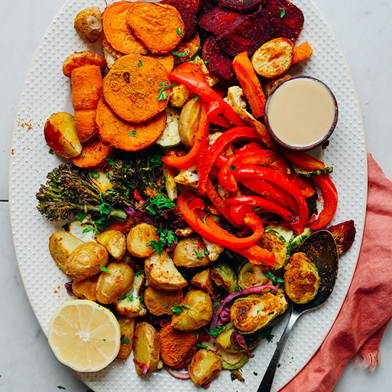 Platter of Oil-Free Roasted Vegetables with a bowl of tahini and a lemon half