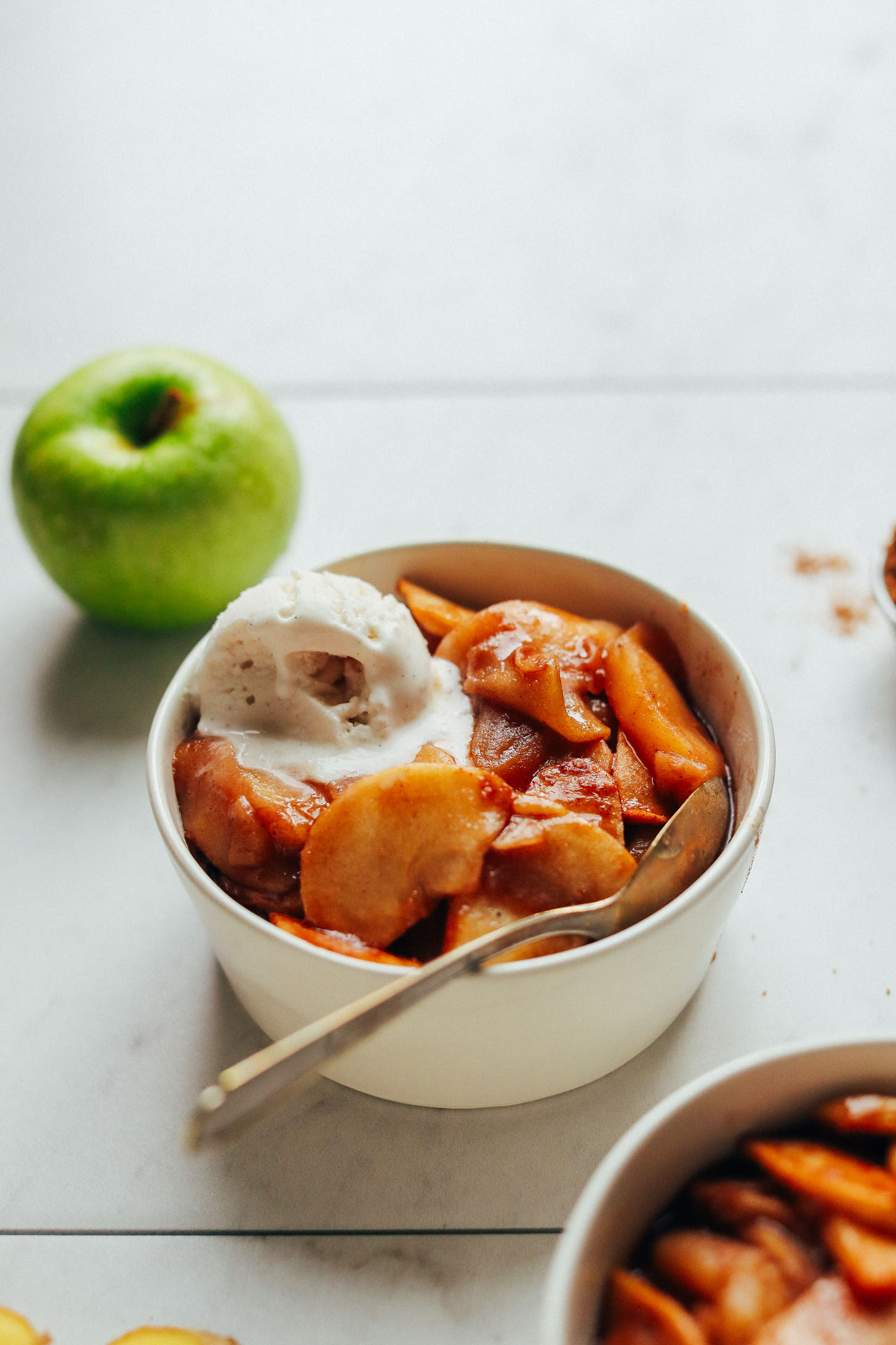 Close up shot of a bowl of Cinnamon Baked Apples with a scoop of vegan ice cream