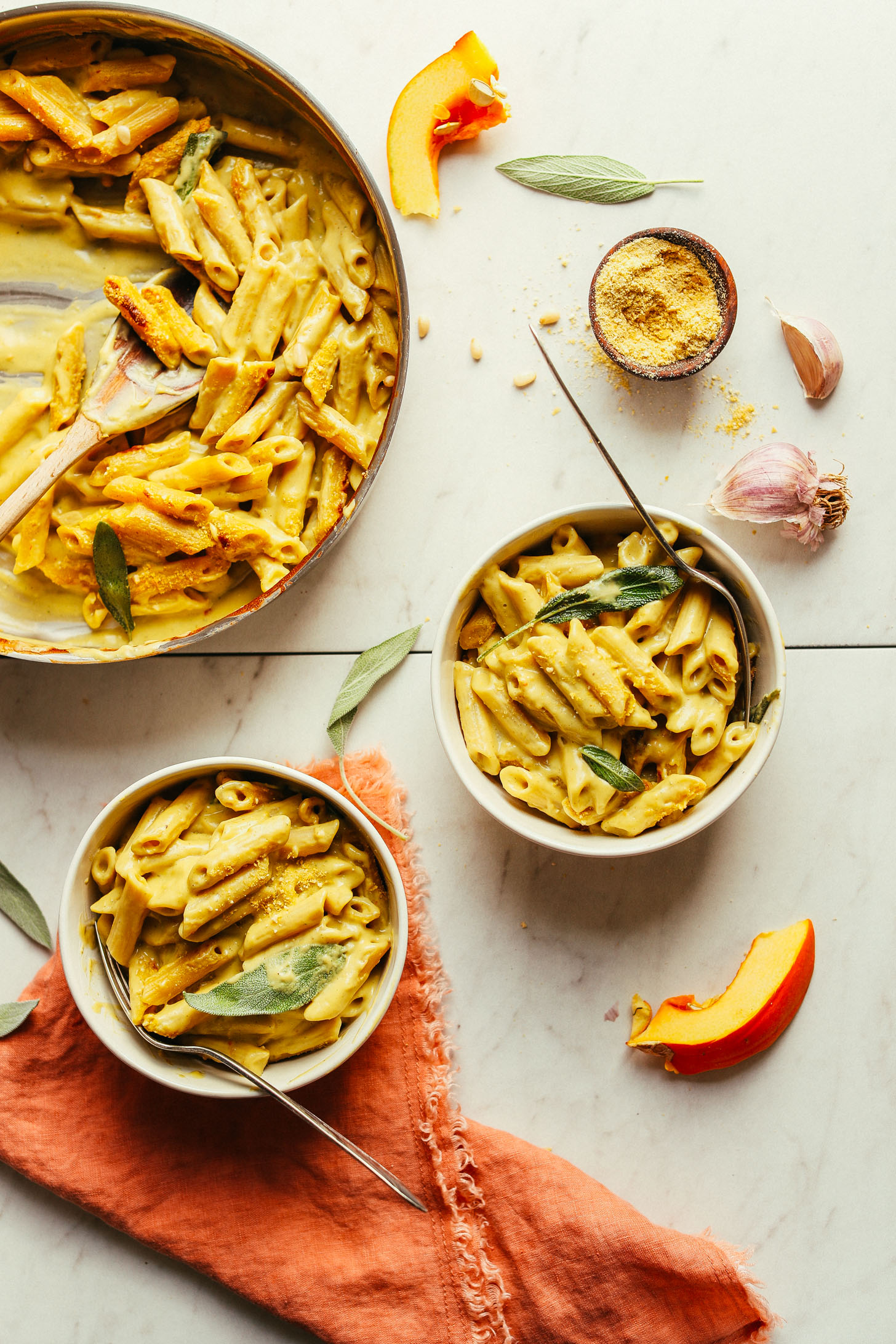 Serving two bowls of Pumpkin Mac 'n' Cheese from a large saute pan