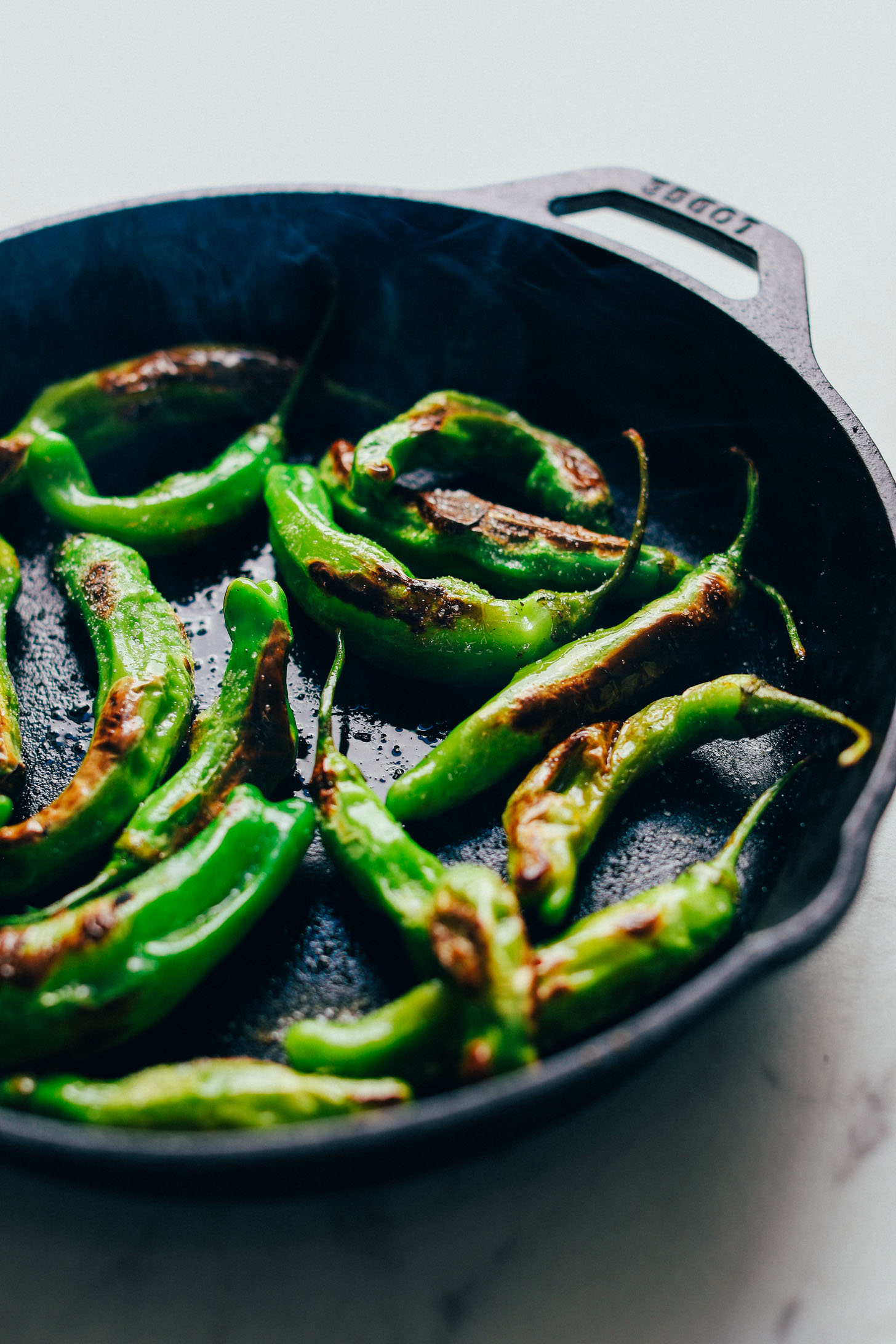 Pan roasting shishito peppers in a cast iron skillet