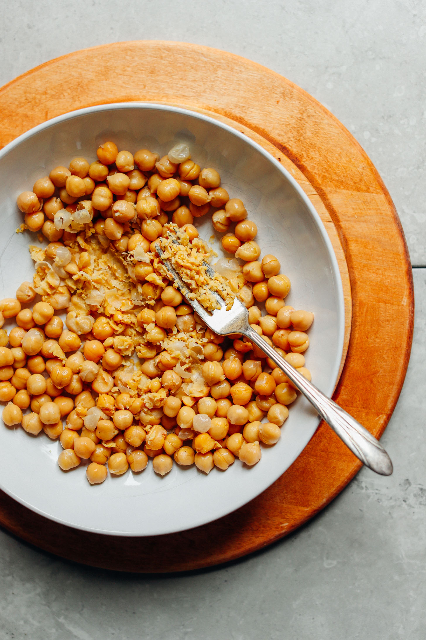 A plate of fiber- and protein-packed chickpeas showing some gently smashed by a fork