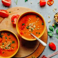 Two bowls of comforting Romesco Soup with Smashed Chickpeas surrounded by fresh ingredients for the perfect plant-based meal