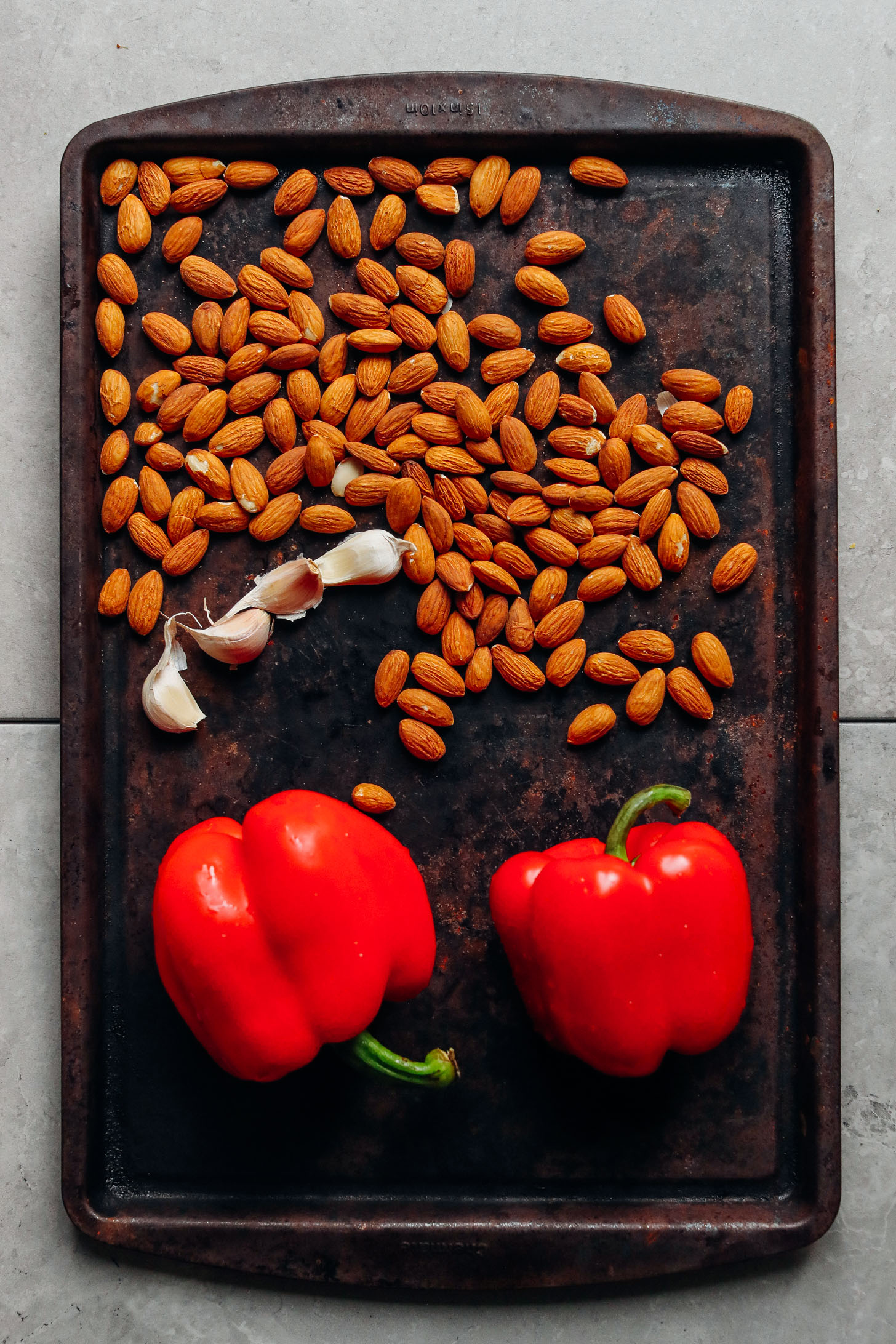 Baking sheet displaying almonds, red bell peppers, and garlic ready for roasting