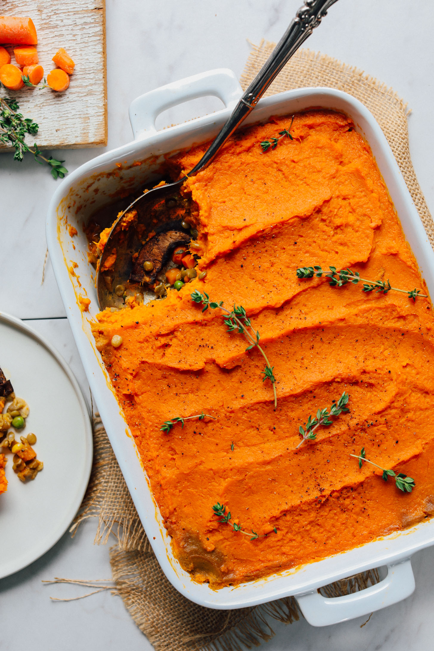 White ceramic baking dish filled with Lentil Shepherd's Pie with a Sweet Potato Crust