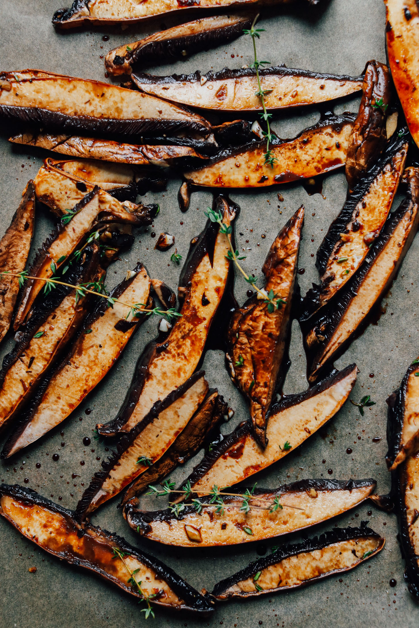 Beautifully roasted eggplant spears with fresh thyme on a baking sheet
