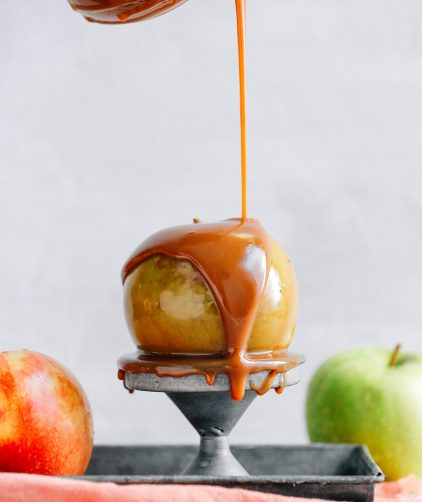Drizzling our AMAZING Vegan Caramel Sauce onto an apple perched on a metal stand