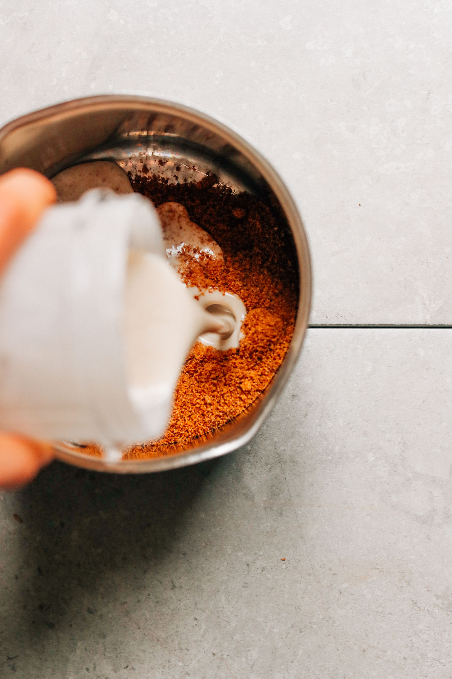 Pouring coconut cream into a saucepan filled with ingredients for making plant-based Caramel Sauce
