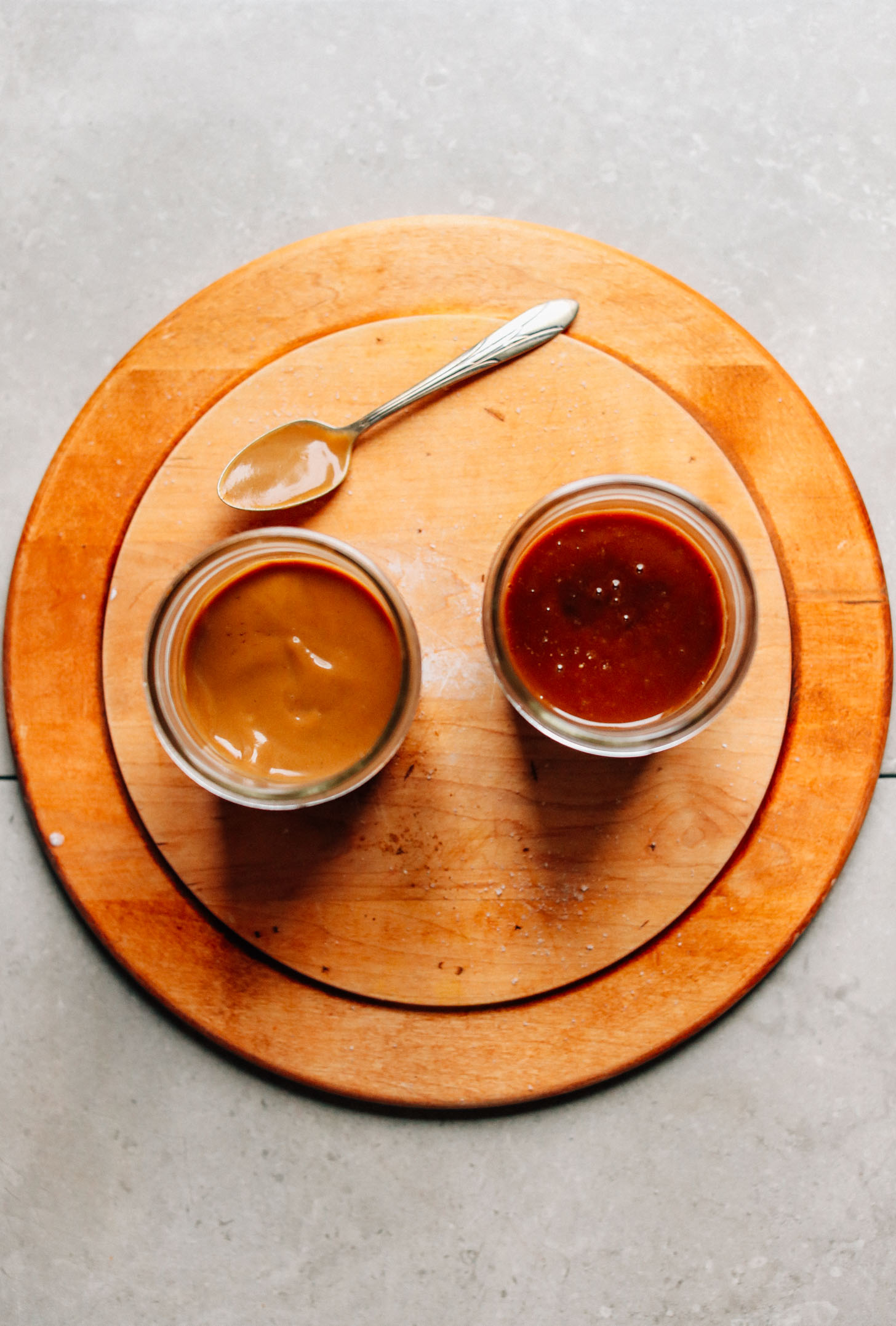 Two jars of refined-sugar-free Vegan Caramel Sauce on a wood cutting board with a spoon
