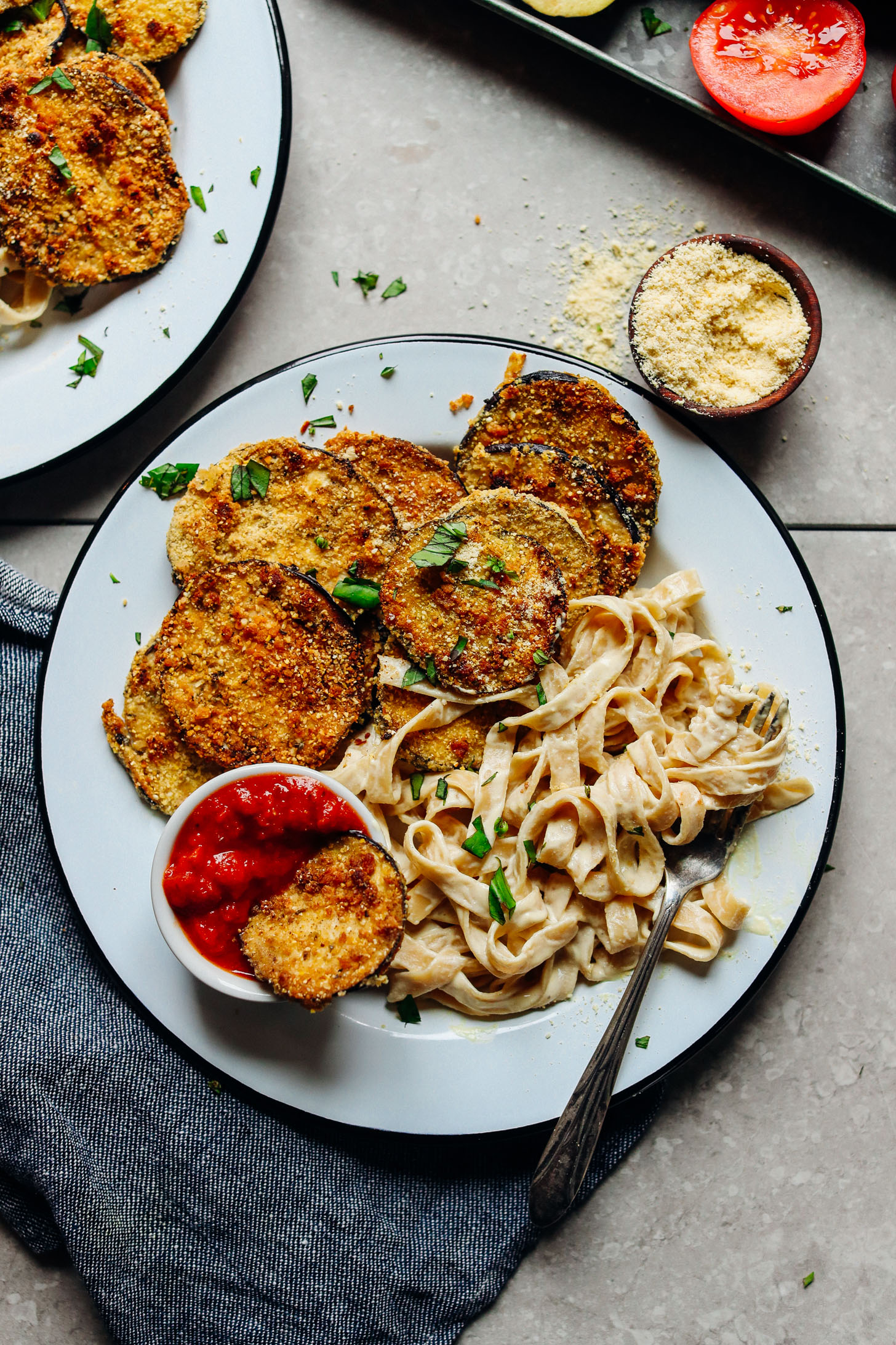 A big plate of gluten-free vegan comfort food including Crispy Eggplant Parmesan with marinara dipping sauce and a side of gluten-free pasta