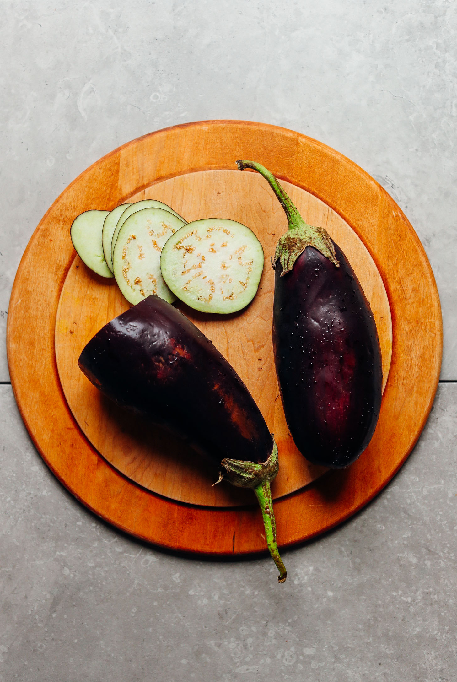 Whole and sliced eggplant on a wood cutting board