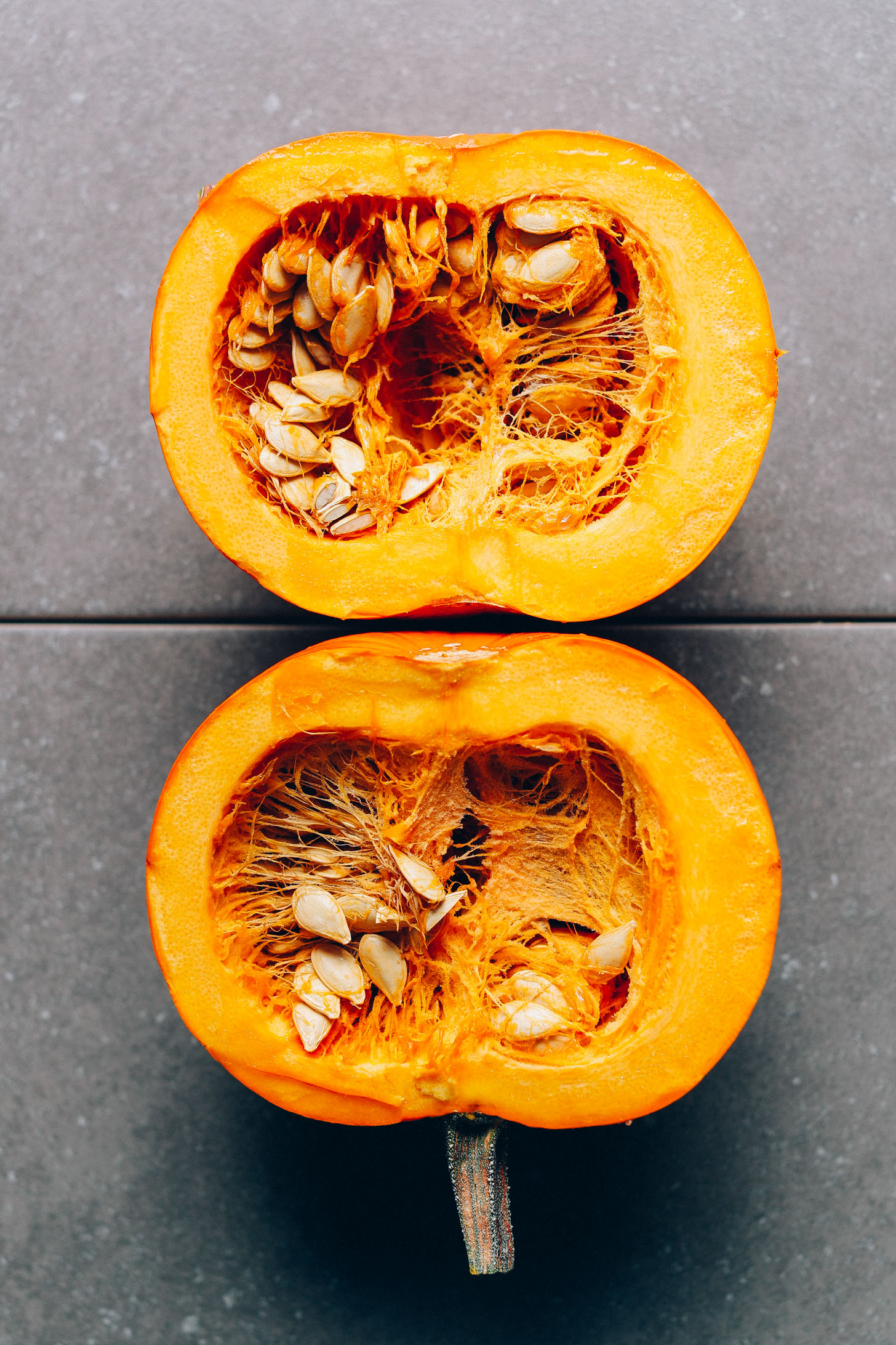 Pumpkin cut in half to show the seeds and rich orange color of the flesh