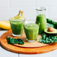 Glasses and a jar of our Avocado Green Smoothie alongside ingredients used to make it