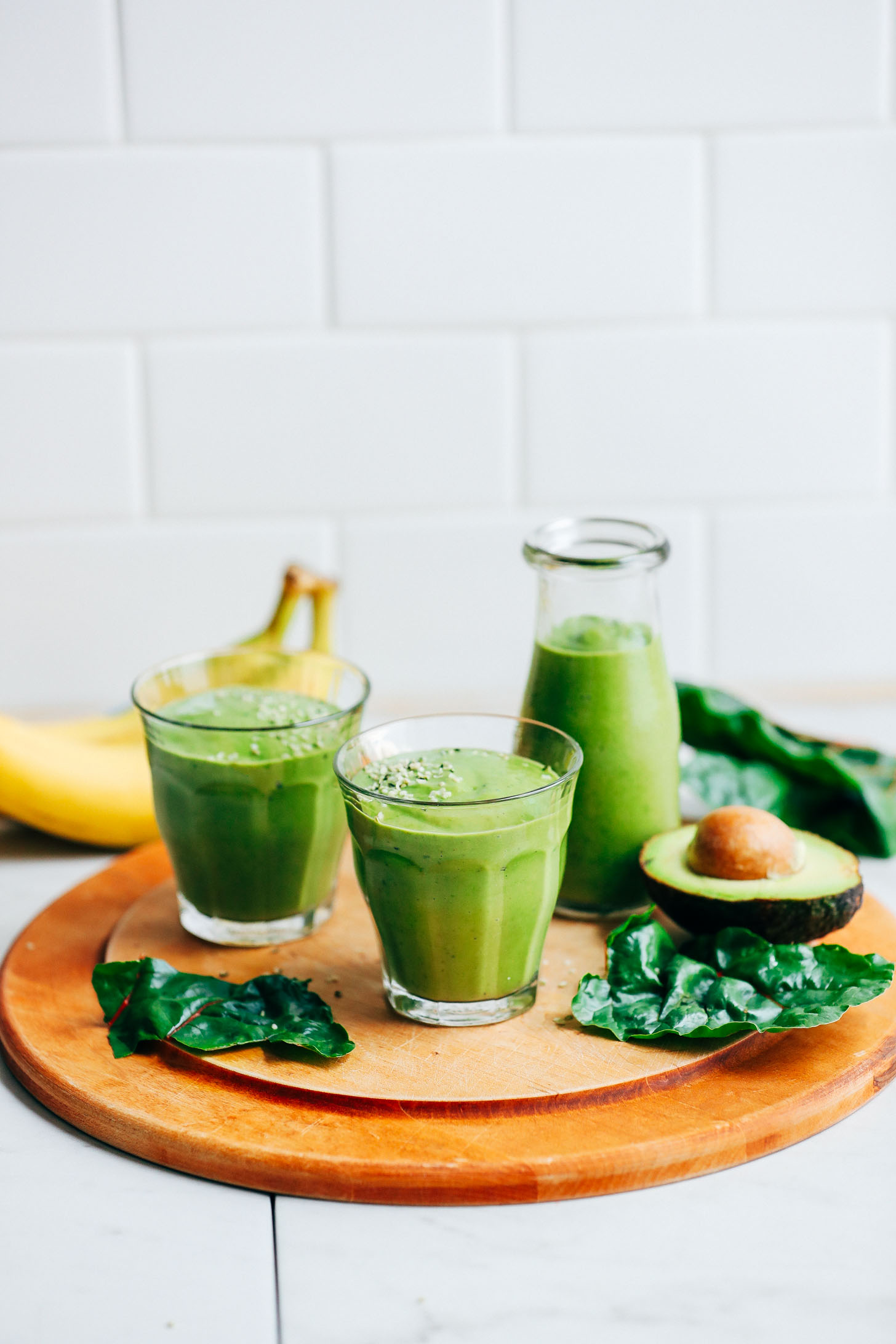 Two serving glasses filled with vibrant Avocado Green Smoothie and surrounded by avocado, banana, and kale