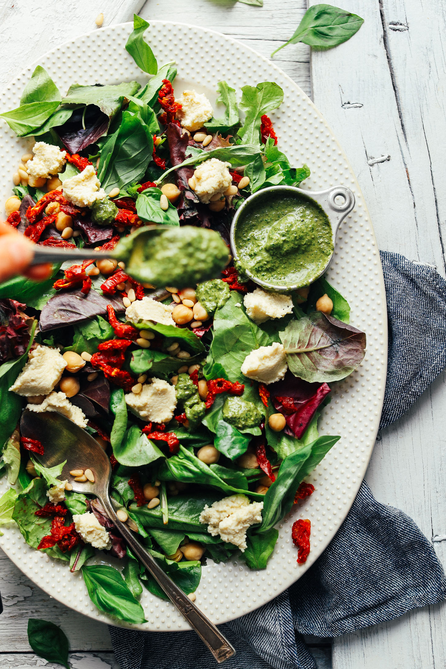 Using a spoon to drizzle Vibrant Pesto over salad with almond ricotta and sun-dried tomatoes