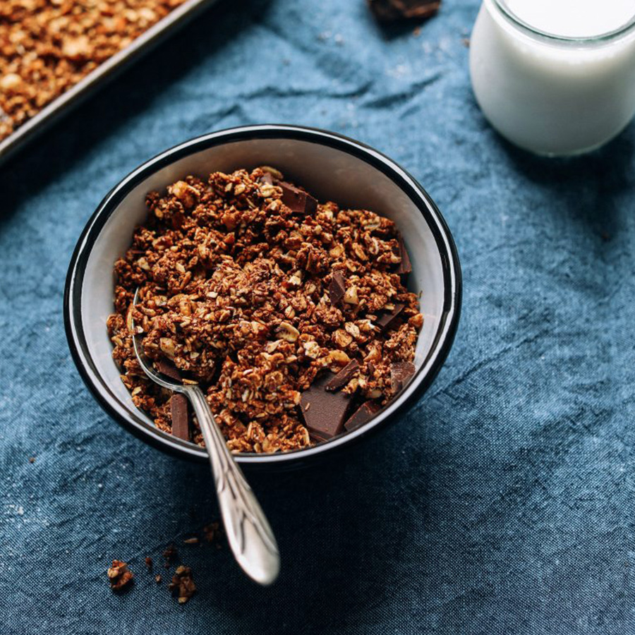 Bowl of Dark Chocolate Sea Salt Granola and a glass of almond milk for our Easy Vegan Breakfast Ideas roundup