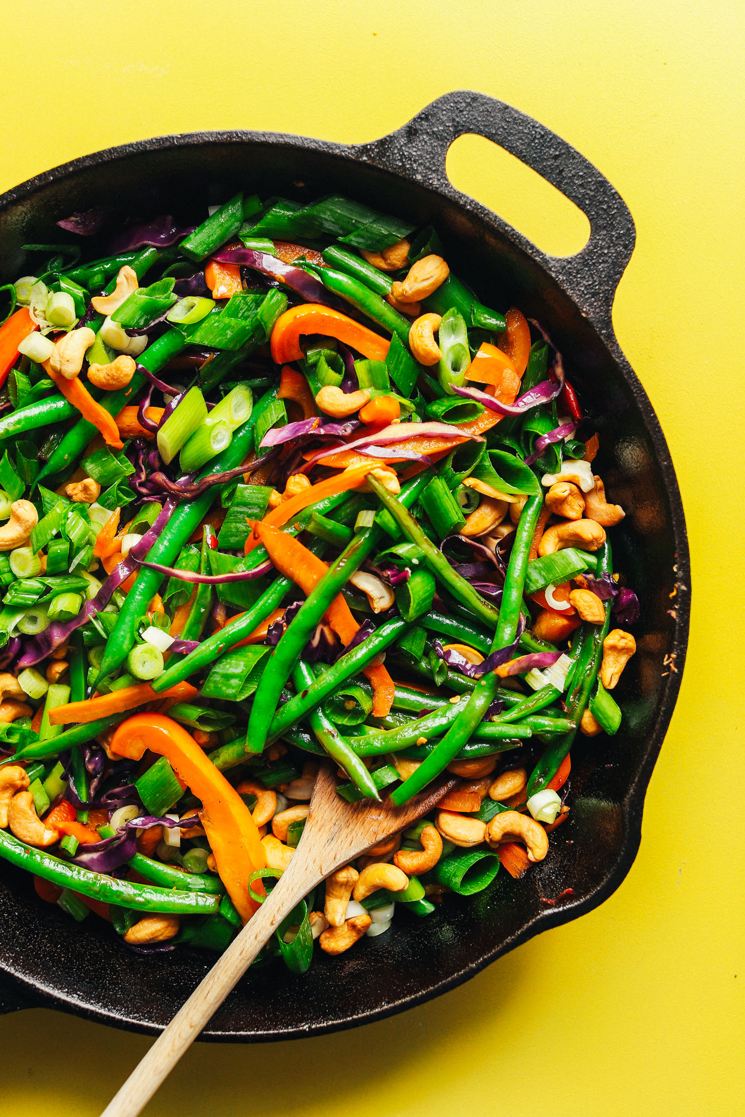 Cast iron skillet with colorful fresh vegetables for satisfying vegan Cauliflower Rice Stir Fry