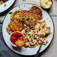 Plate of Crispy Gluten-Free Eggplant Parmesan alongside fettucine noodles and marinara