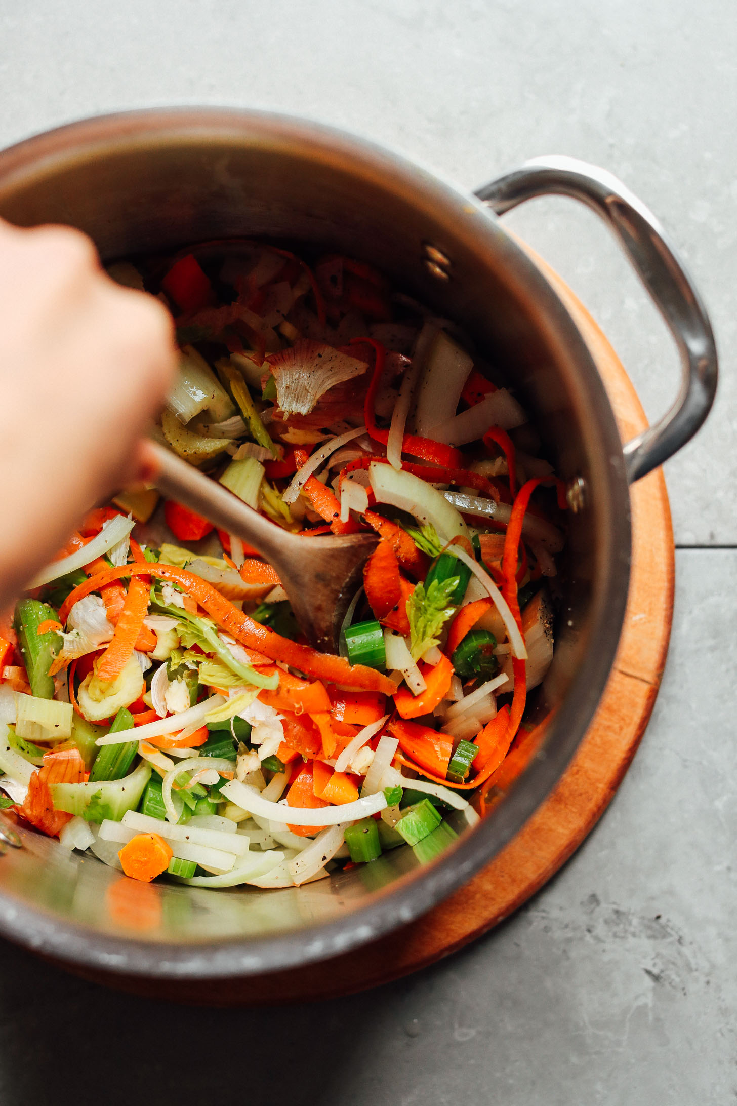 Stirring a big pot with vegetables for making the BEST homemade vegetable broth