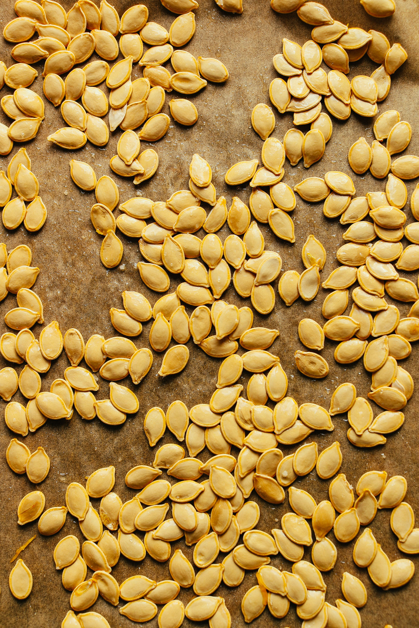 Parchment-lined baking sheet with pumpkin seeds for making Roasted Pumpkin Seeds