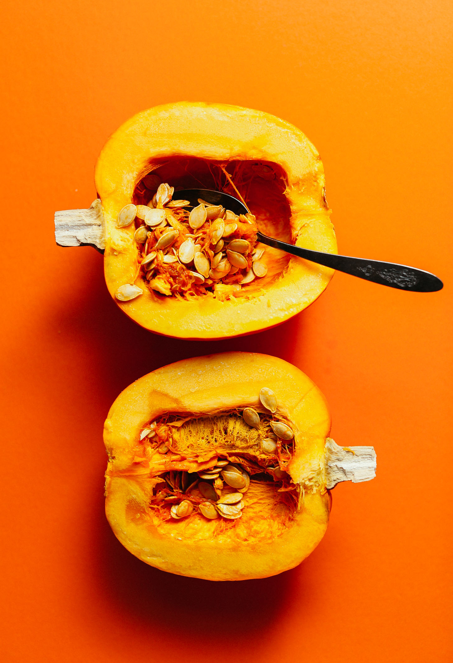 Scooping out the seeds and flesh from a halved pumpkin